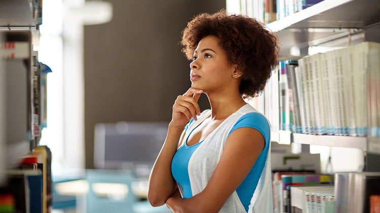 An African American high school student choosing book at library.