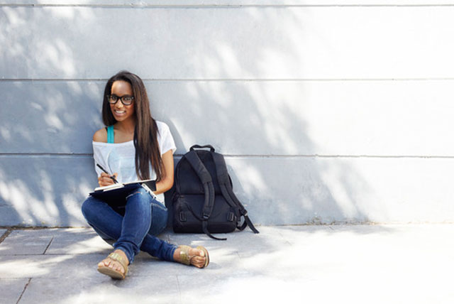 Young student siting outside writing a list of colleges
