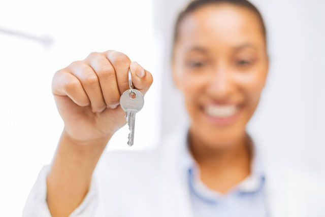 female college student with hand holding up first apartment keys