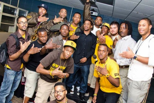 Black Fraternities: A group of Iota Phi Theta members pose for photo in brown and gold fraternity colors.