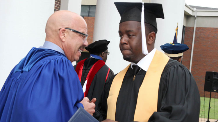 Tom Joyner congratulates a full ride scholar and Stillman College graduate at his Commencement Ceremony.
