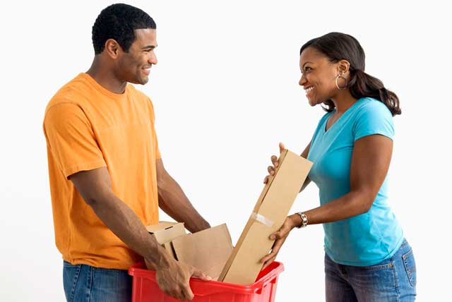 African American male college student holds a bin while pretty female puts cardboard into it for winter break jobs.