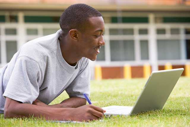 African-American male student using laptop on lawn while applying for college online.