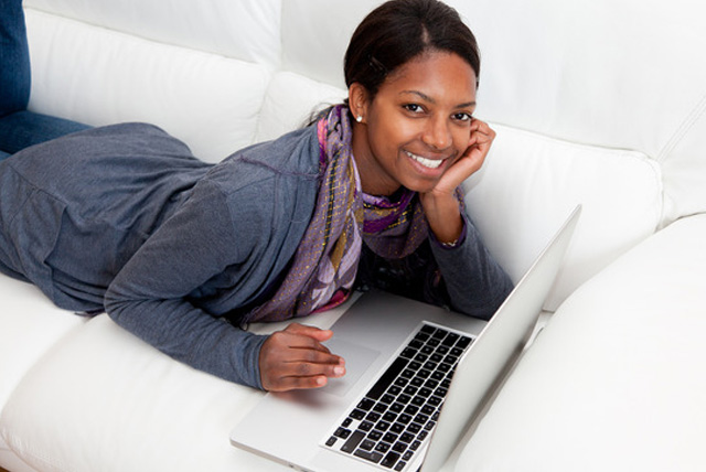 Smiling African American students using computer to apply for HBCUs using the Common Black College Application online.