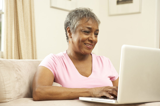 Non-Traditional Students: African American Senior working on college assignment on laptop.