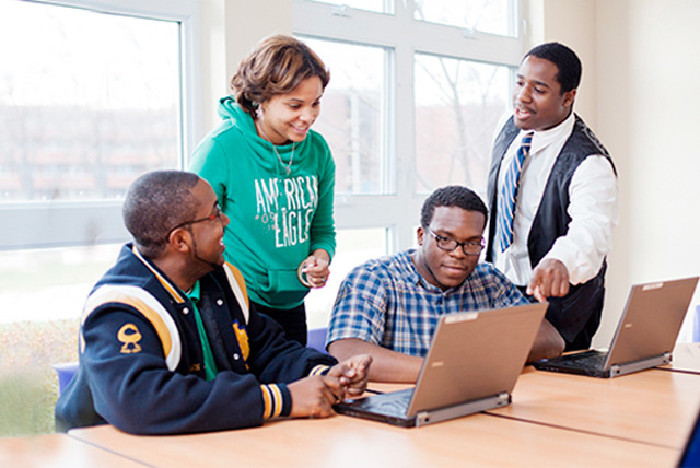 Best Online Graduate Programs: North Carolina A&T students collaborate on an a computer technology project with professor.