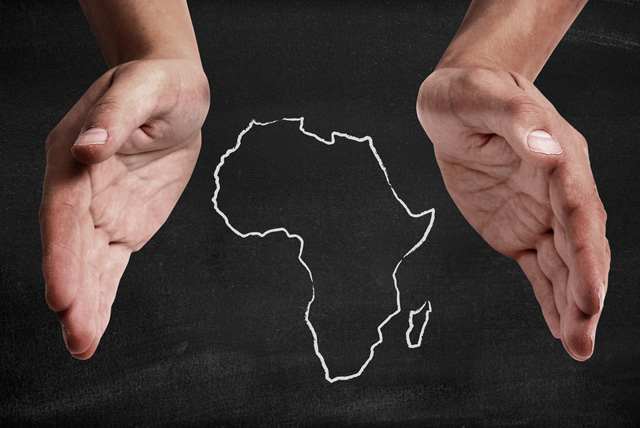 African Diaspora: Black hands supporting chalk drawn image of Africa.