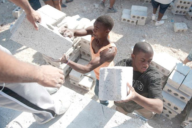 Peace Corps 2014 Top HBCUs: Howard University volunteer participants work alongside Haitian locals to unload a truck of bricks used for the completion of a school wall.
