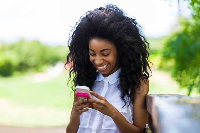African-American HBCU student using a smart phone to manage her side hustle gigs.