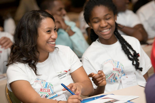 Two female African American students enjoy listening to a guest speaker at the 2013 Gates Millennium Scholars CA Freshman Leadership in California. Applications are open for the Bill Gates Scholarship through January 14, 2015.