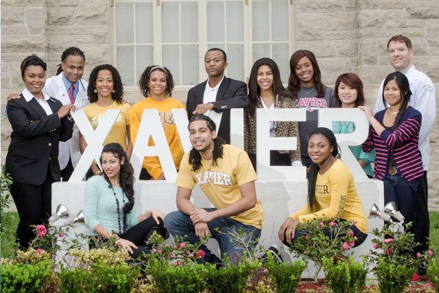 Proud Xavier University of Louisiana students pose in front of historic school sign.