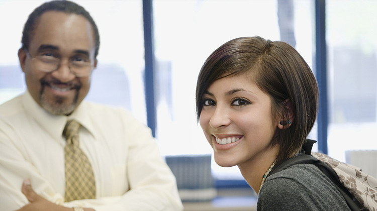 Portrait of academic advisor and college student smiling together while discussing educational plans.