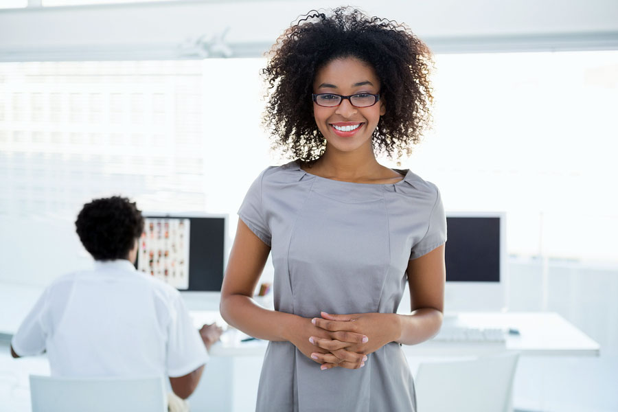 Young African-American editorial intern smiling at camera with colleague working behind her in magazine offices.