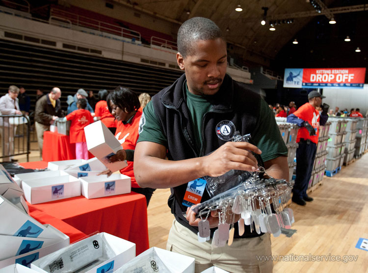 An AmeriCorps member prepares items to pack in kits for overseas troops at the DC Armory during 2013 National Day of Service and MLK Day activities.