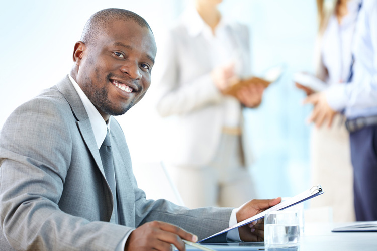 Young Black professional is smiling at his dream job.