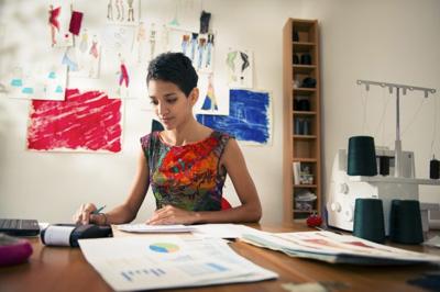 African American female fashion designer sitting at desk using a calculator.