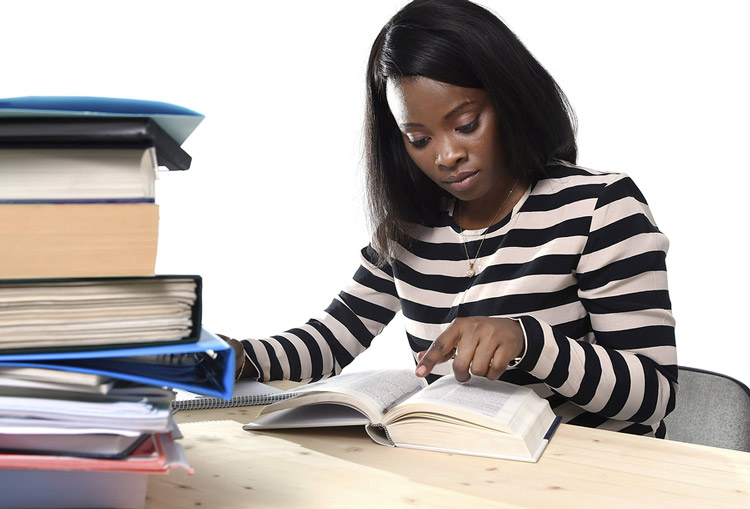 Young African-American reviewing textbooks in preparation for an exam.