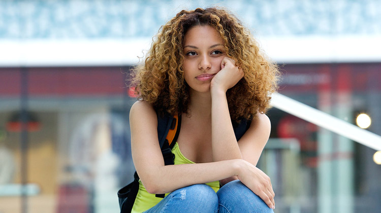 African American female college student sitting outside with worried expression on face.