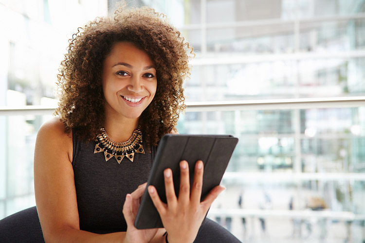 Young African American college student using a tablet computer at her first internship.