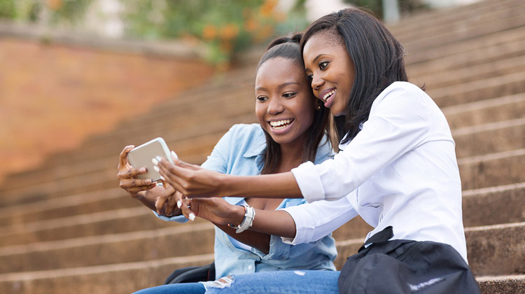 Female African American roommates in college using cell phone to take a selfie on campus
