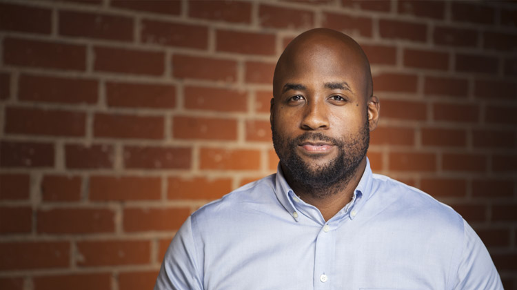 Kareem Taylor, a Clark Atlanta University graduate and voiceover artist poses in front of a brick wall backdrop.