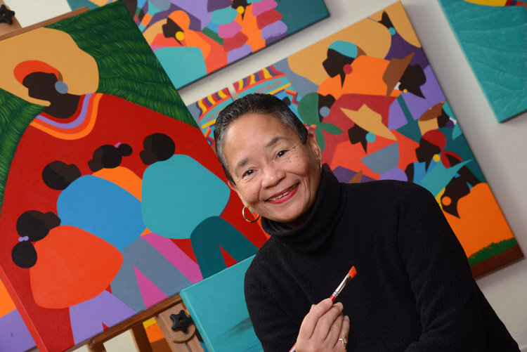 Renowned visual artist Synthia Saint James poses holding a brush with paint in front of her iconic paintings.
