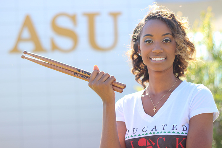 Percussionist Jazz Kelley poses holding her drumsticks at Albany State University.