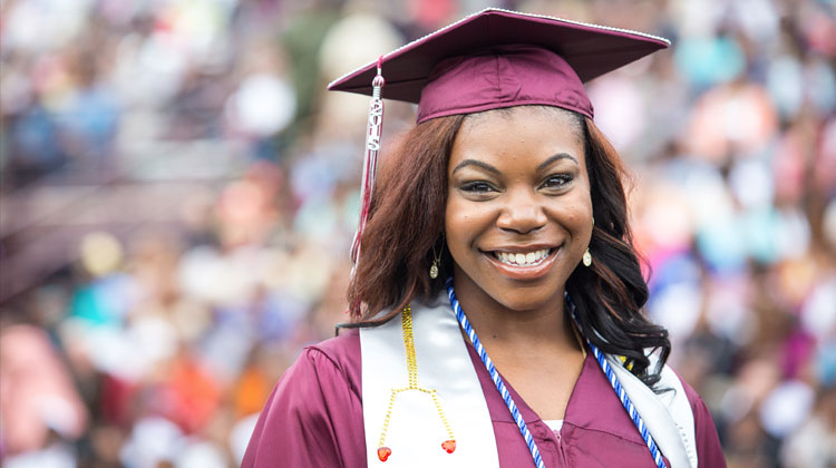 Top Minority Degree Producers: A North Carolina Central University student smiles in her cap and gown during a 2015 graduation commencement ceremony.