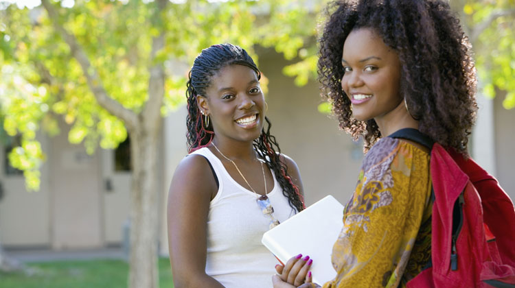 Two female Black College students talking together on campus.