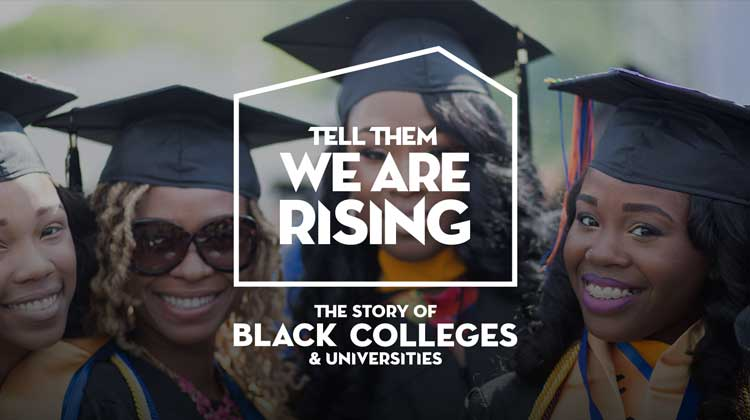 Four female HBCU graduates are wearing caps and gowns smiling in a group photo.