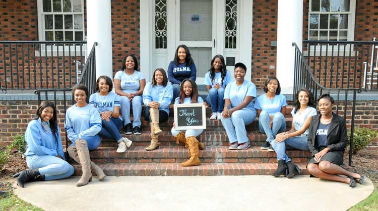 Spelman Students sit on steps holding a thank you sign on the campus of the historically black liberal arts college.
