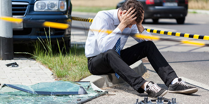 Vehicular Manslaughter lawyer tampa - Man sitting on side or road holding his head after accident