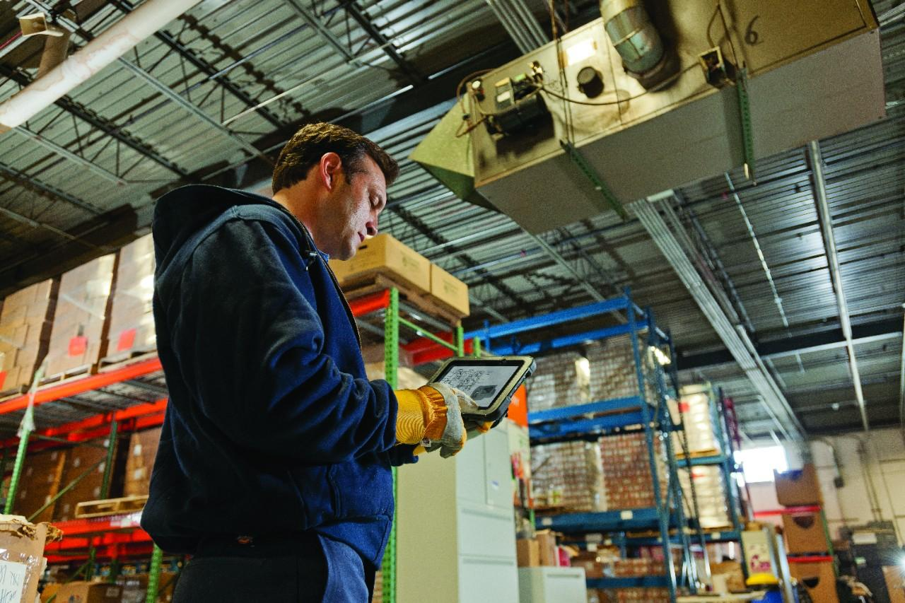 Warehouse Worker Solving Solutions Using a ET50 Tablet to Check Inventory