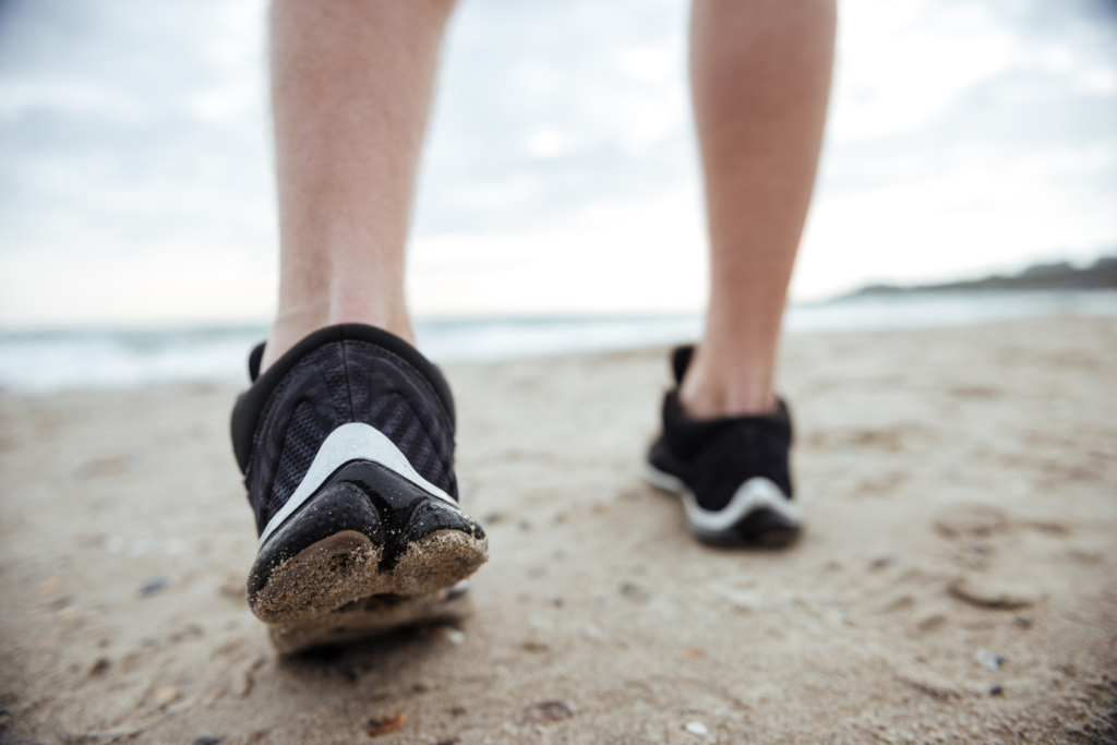 woman's feet walking on the beach to recover from a sugar binge