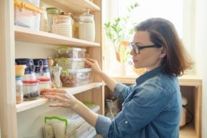 woman looking through pantry after being diagnosed with a food allergy