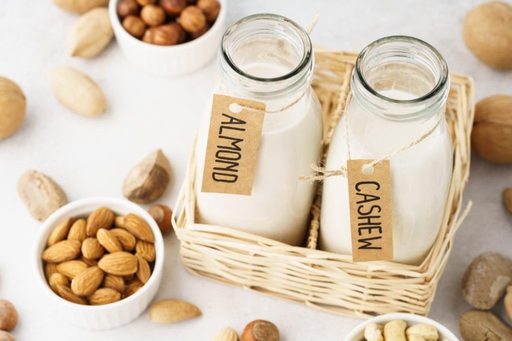 Dairy Free milk made of nuts in glass bottles with bowls of almond and cashew