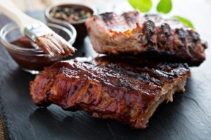 Grilled pork ribs with bbq sauce on black slab