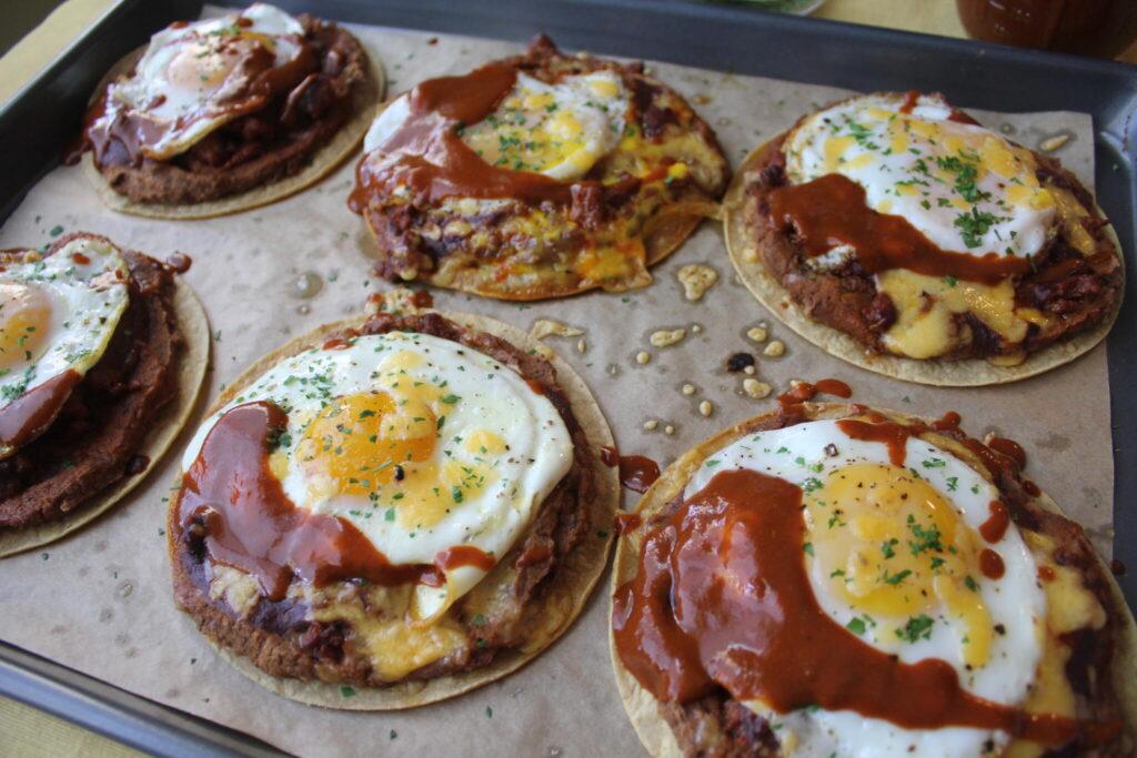 a baking sheet of individual huevos rancheros