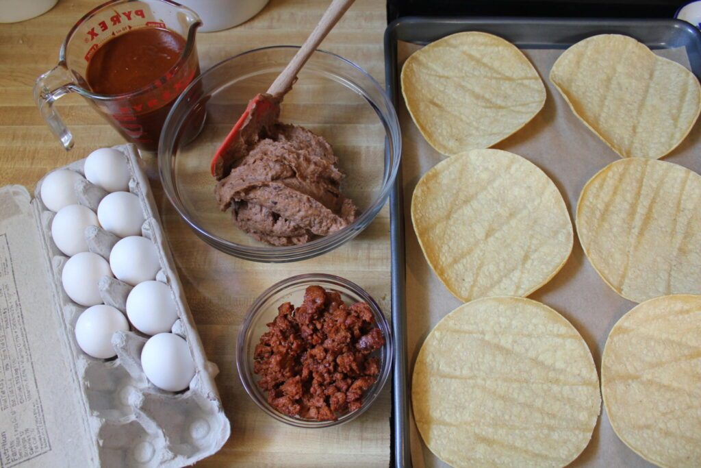 all the ingredients to make huevos rancheros pizzas on the counter ready to assemble