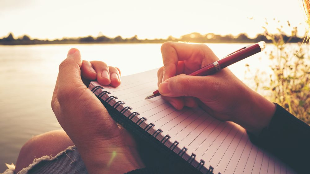 woman writing in an allergy free food journal