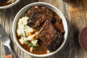Slow cooked Braised Beef Short Ribs in a bowl with dark brown Gravy and Potatoes