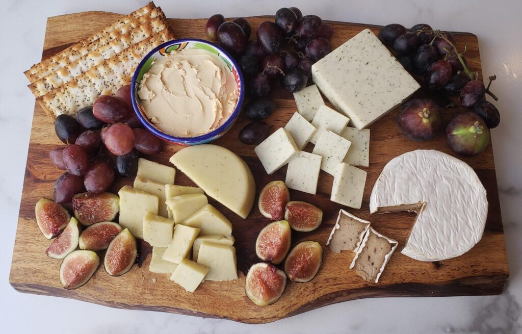 a wood board with dairy-free cheeses and fruits and crackers