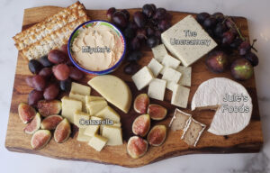 Dairy free cheeses on a wood board with the brand names of each cheese overlayed