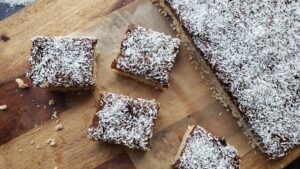 Apricot and Coconut Shortbread Bars cut into squares on a wood cutting board