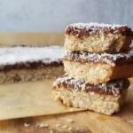 stack of apricot plum coconut bars on a wood cutting board