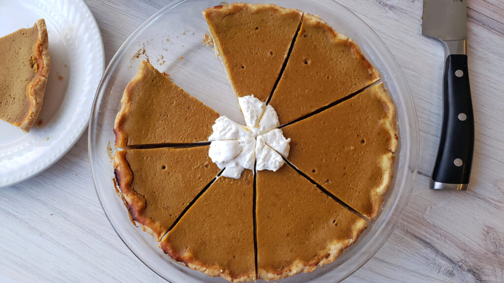 Pumpkin pie cut into slices in a glass pie dish
