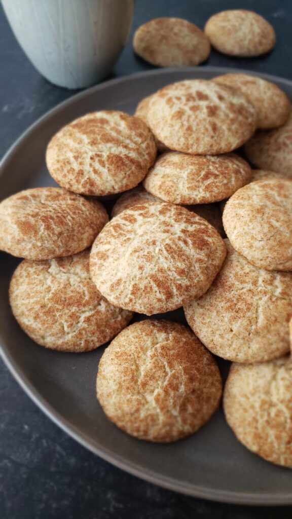 snickerdoodle cookies on a dark plate with coffee in background