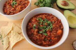 Big Batch Chili Recipe in bowls surrounded with tortilla chips and avocados