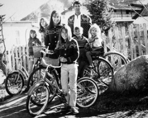 A slide of the Hayes Family, 1967. The image shows Jim and Mary Eshbaugh Hayes with their children; Pauli, Ellie, Laurie, Clayton and Bates. They are posed with bicycles in their backyard and are all wearing Nordic sweaters.