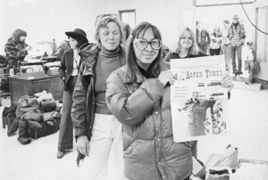 A photograph of Jill Sabella (left) looking at Mary Eshbaugh Hayes (right) holding up a newspaper from October 6, 1977 where pressman Blue Neal can be seen on the front page. Behind them are various other unidentified people in the press room of the Aspen Times and at the door of the room.
